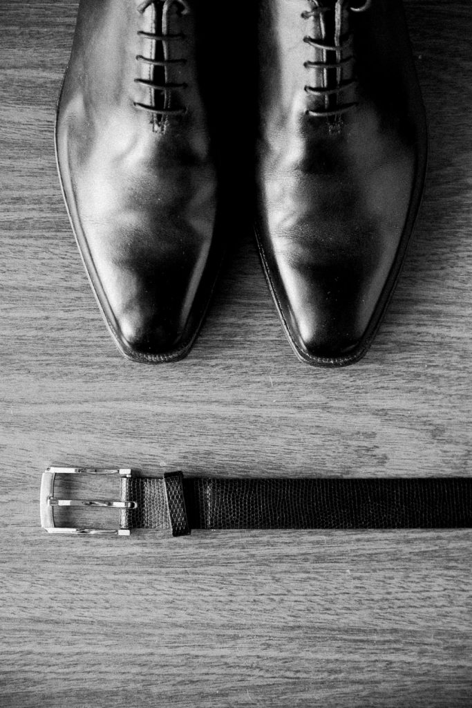 Grooms shoes and belt placed on a wooden table.