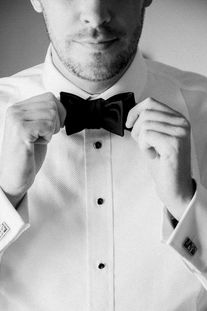 The groom is holding his bowtie.