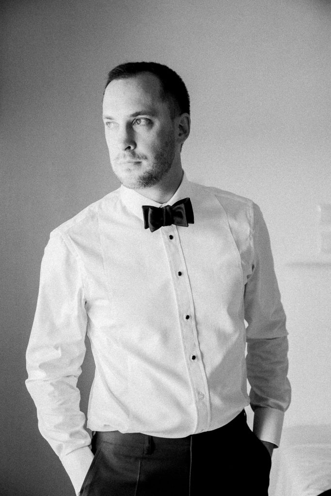 The groom wearing his white shirt and black bowtie has his hands in his pockets.