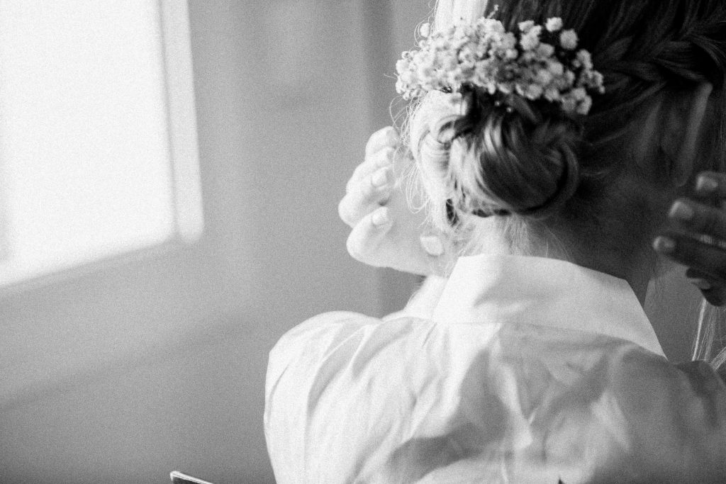 The bride is holding her hair that has flowers .