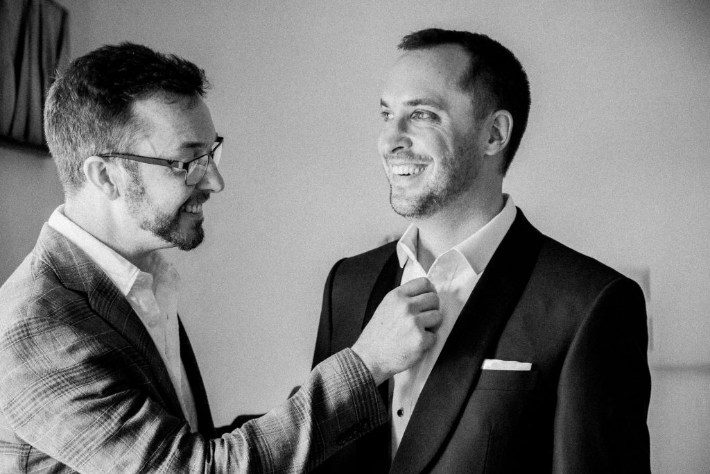 The groom is smiling while his friend is fastening up his buttons.