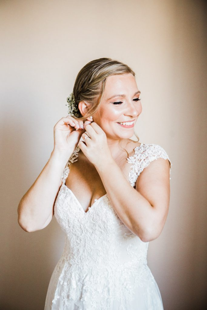 The bride is in her wedding dress putting her earrings in and smiling.