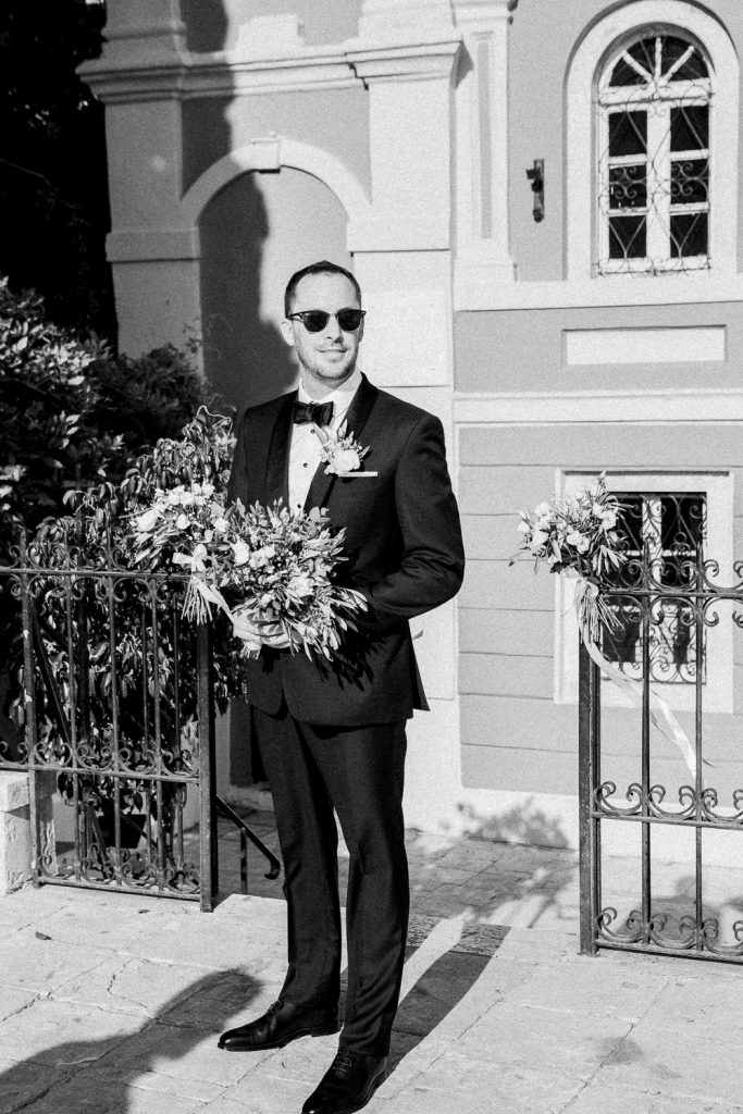 The groom is waiting outside the church holding a bouquet of flowers.