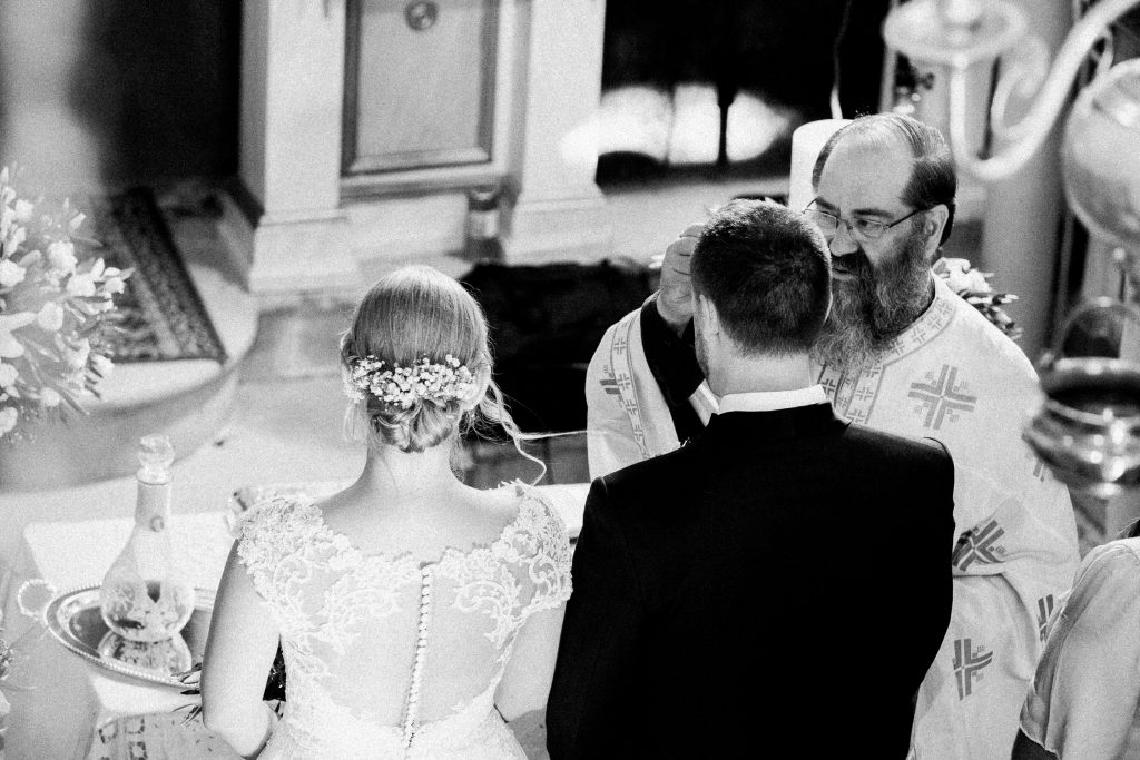 The bride and groom are standing in front of a table with the priest.