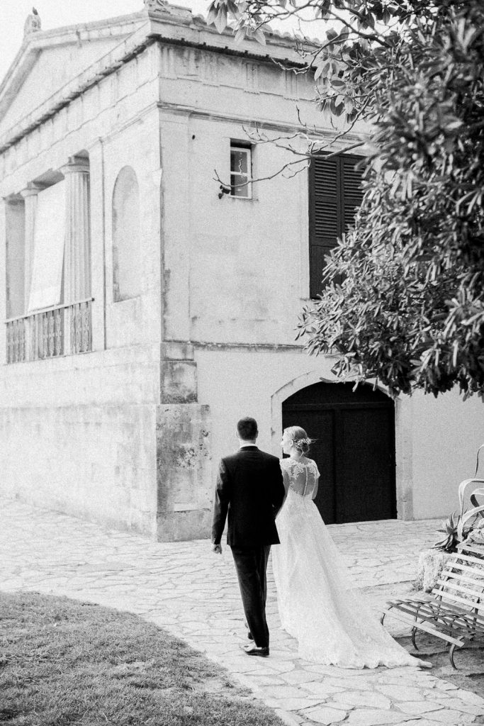The bride and groom are walking on a path next to an old building.