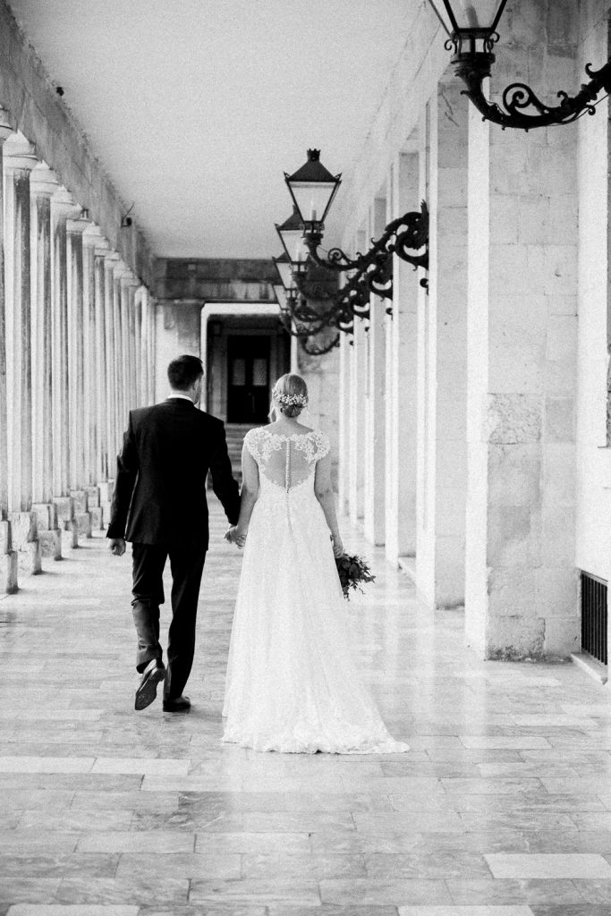 The bride and groom walking with columns and lamp posts either side.
