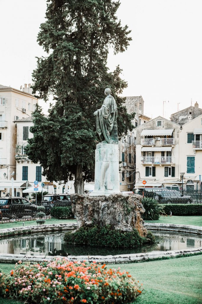 A fountain in the Asian Museum in Corfu surrounded by old buildings.