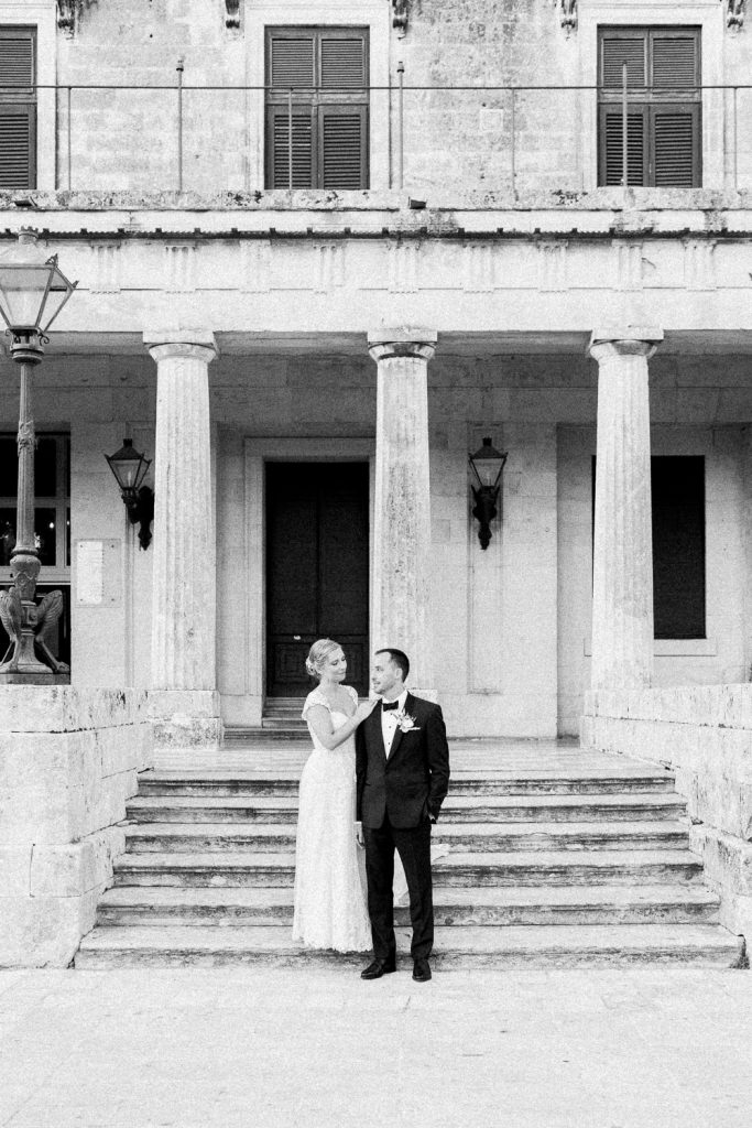 The bride is leaning against the groom and looking at him in front of an old building with columns.