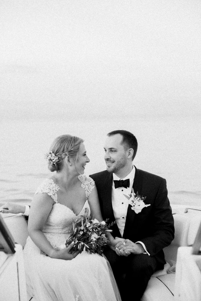 The bride and groom are siting in a boat looking at each other.