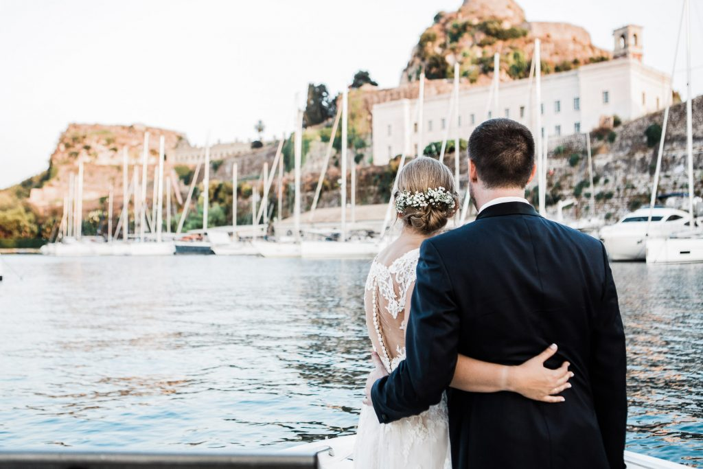 The bride and groom are hugging and looking at Corfu's sailing club.