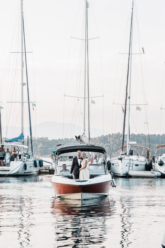 The bride and groom are arriving on a boat hugging and surrounded by other sailing boats.