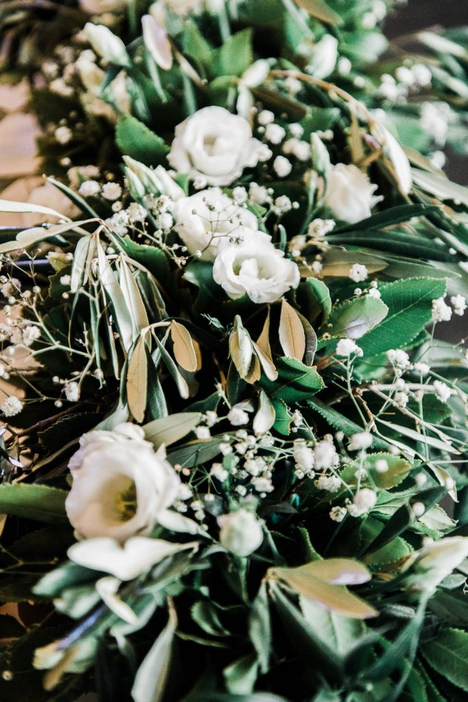 Wedding decorations with white roses and green olive leaves.