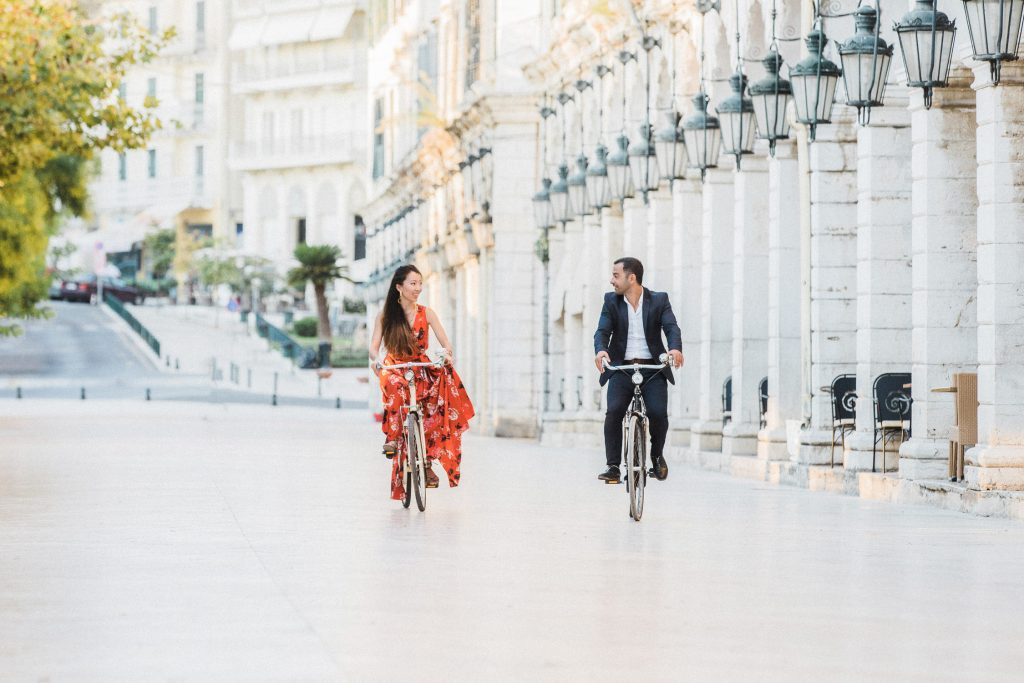 A couple riding bicycles  on the Liston in Corfu looking at each other.