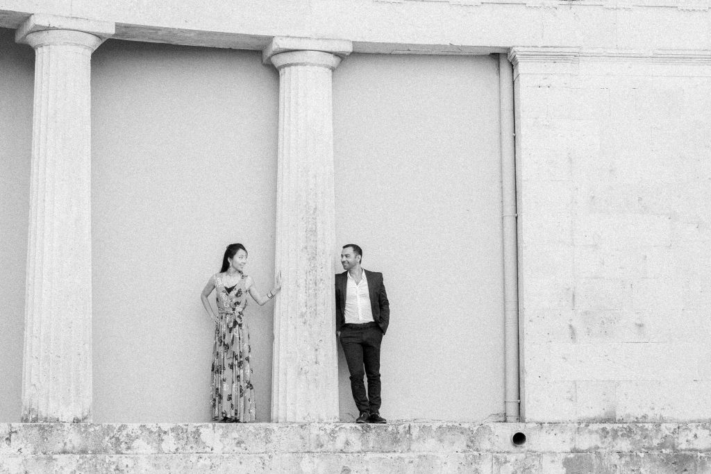 A couple are leaning against an ancient column looking at each other.