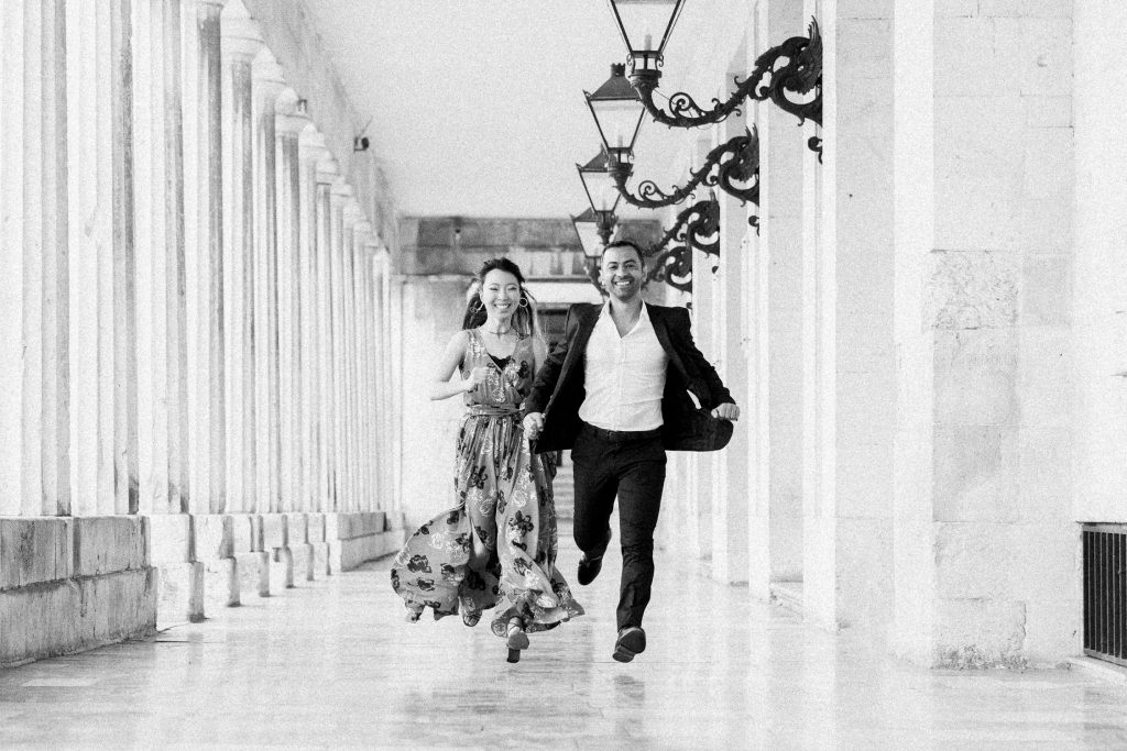 A couple are running holding hands and smiling in between ancient columns and lamp posts at the Asian Museum in Corfu.