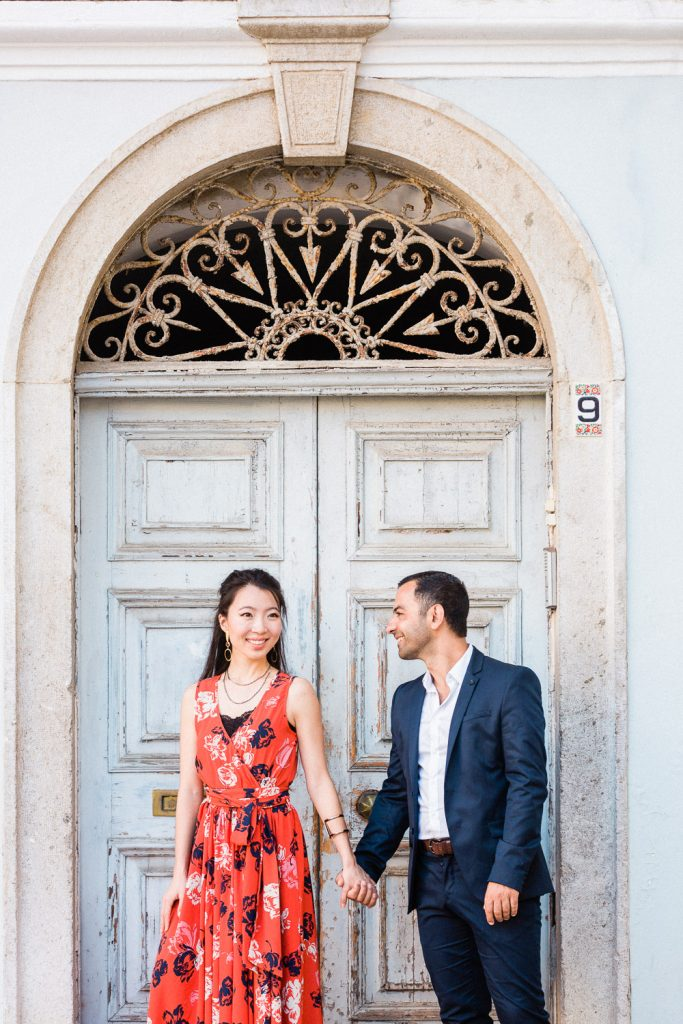 A couple are holding hands in front of an old wooden blue door.