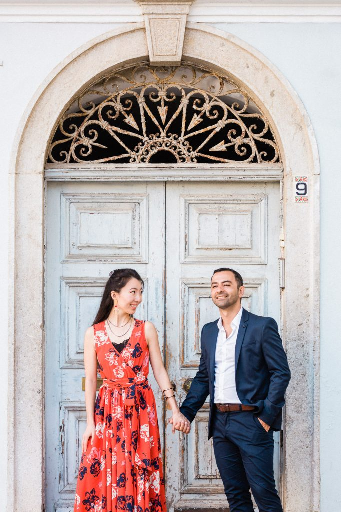 A couple are holding hands in front of an old blue wooden door.