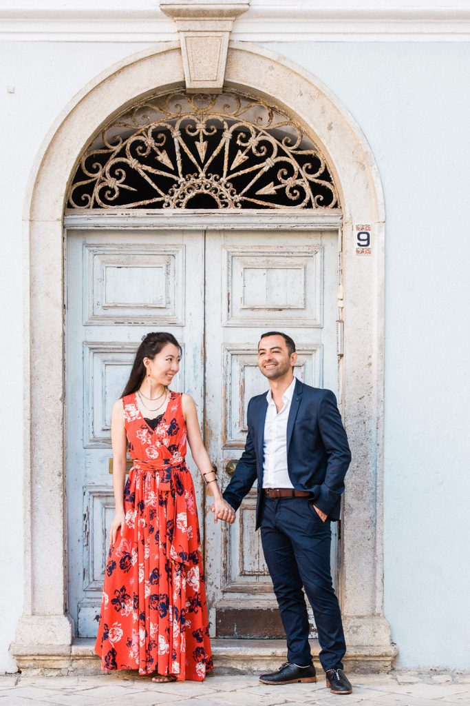 A couple are holding hands in front of an old blue door.
