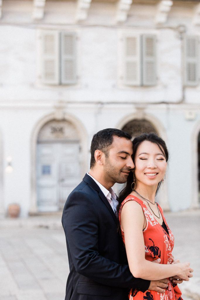 A couple are hugging in front of old buildings with their eyes closed.