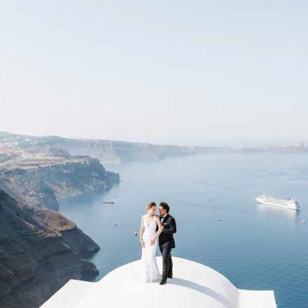 a couple is hugging on the white rooftop overlooking caldera in Santorini