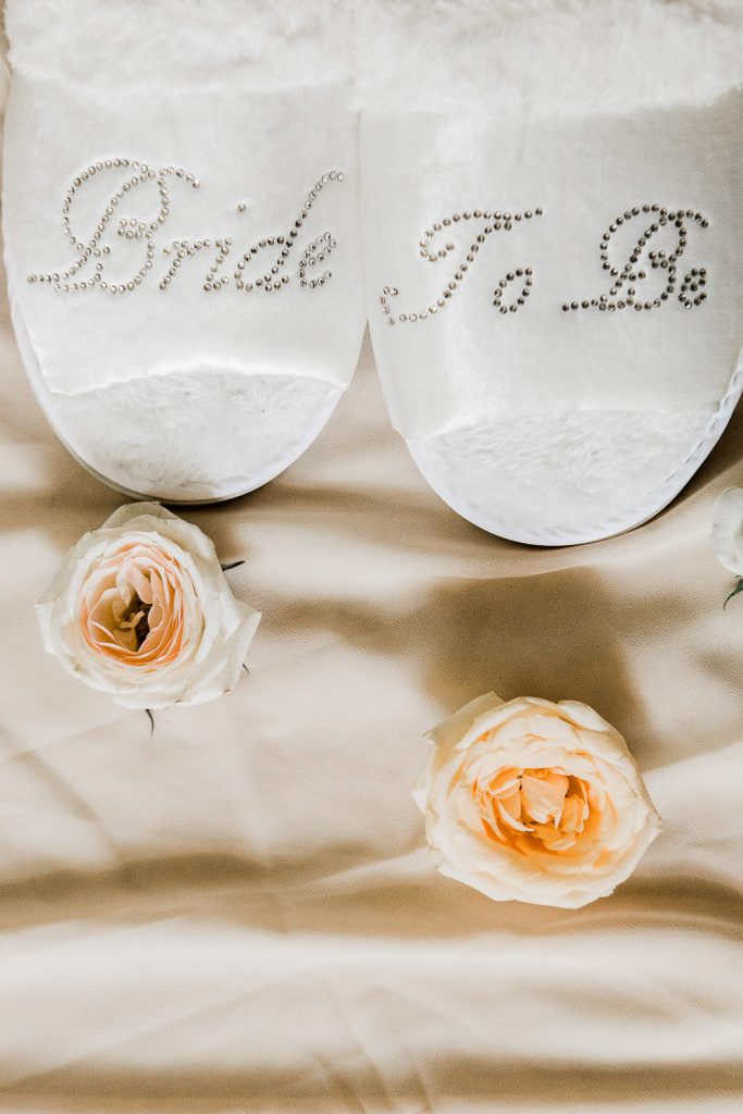 White Slippers with sparkle Bride To Be written on placed nicely on the bed along with white and orange roses.
