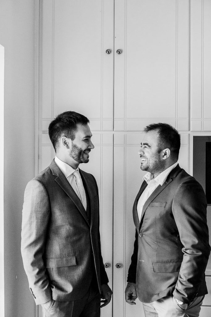 The groom and his brother are standing in front of a white closet wearing suits.