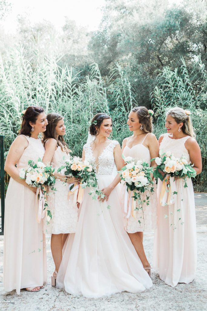 Bride and bridesmaids holding white, orange and green flowers looking at each other in front of green scenery.