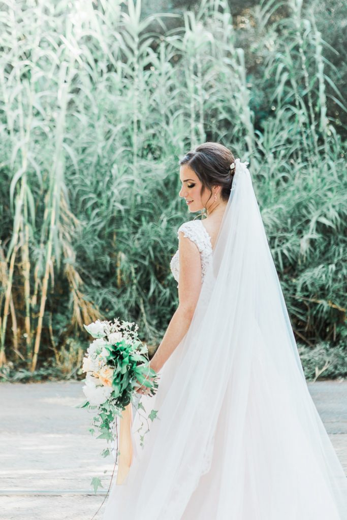 Bride holding her bouquet in her wedding dress and vail in front of a green scenery.