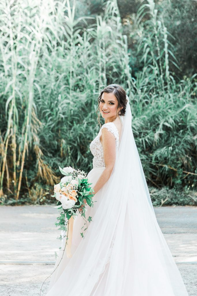 Bride in her wedding dress and vail holding her bouquet in frint if a green scenery.