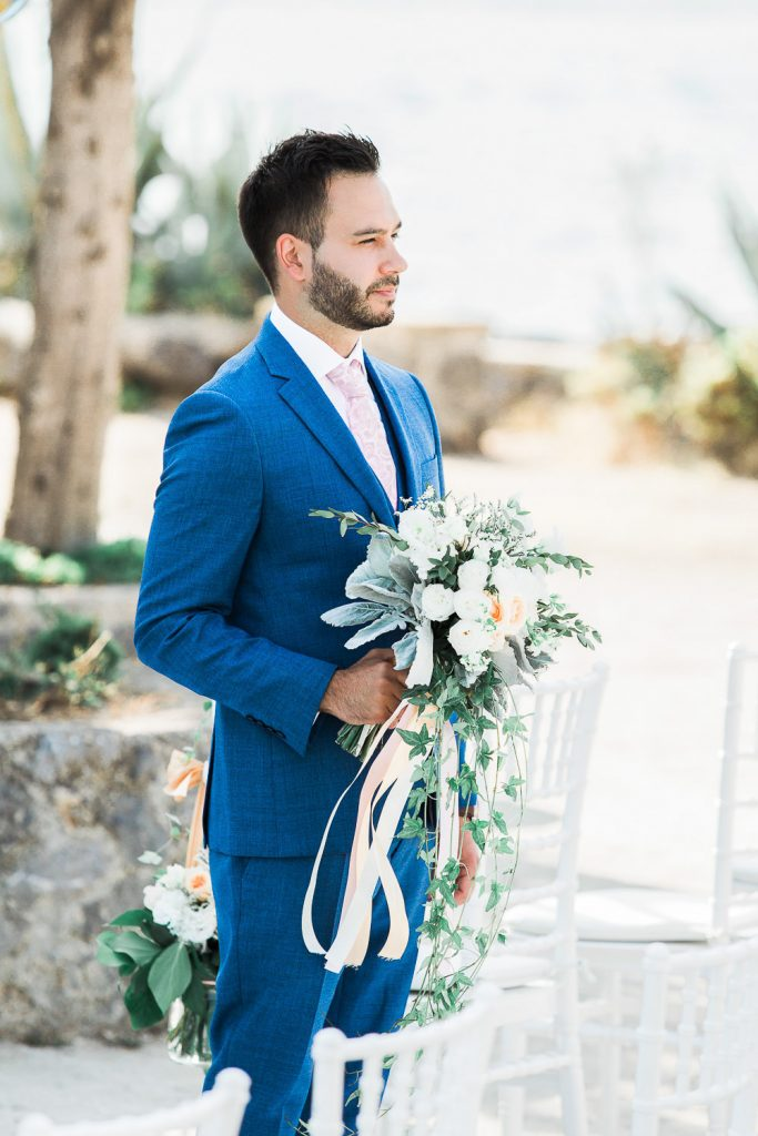 Groom wearing a blue suit and pink tie holding a bouquet.