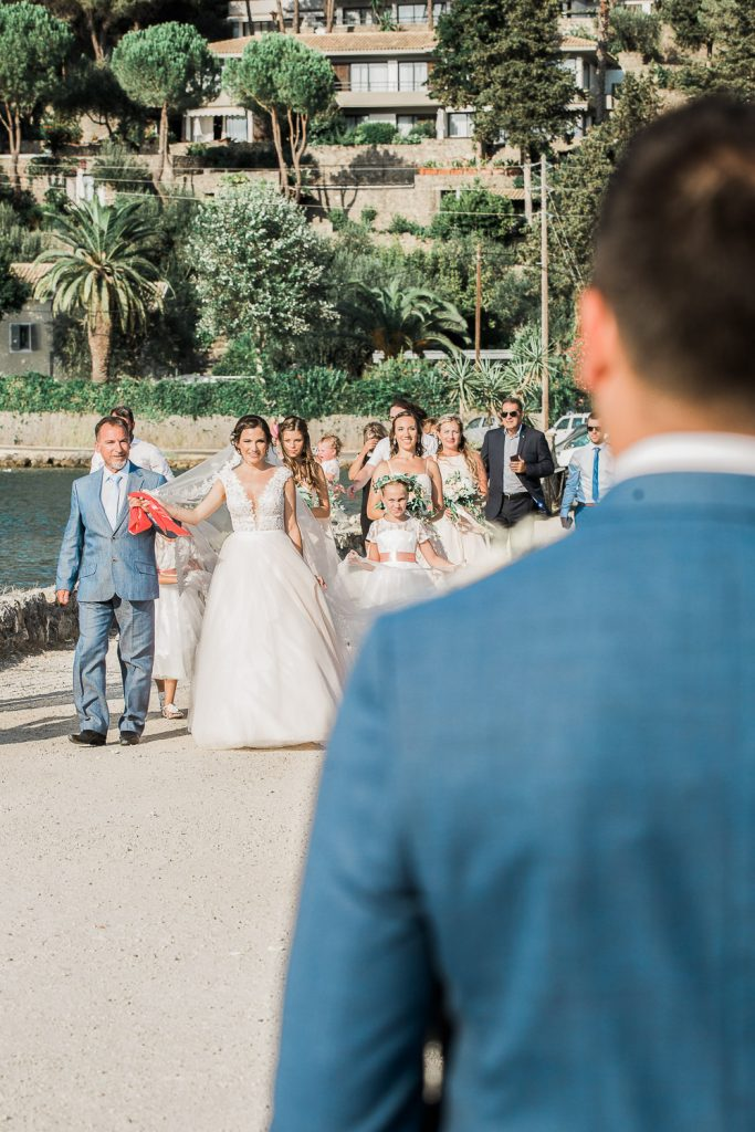 Bride walking up to the church holding a red scarf with her father with family and friends following.