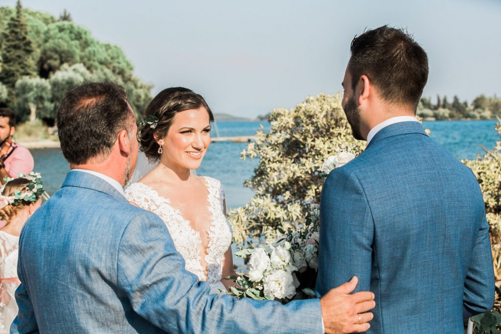 Bride looking at the groom with the her father holding both of them in a green scenery and blue sea.
