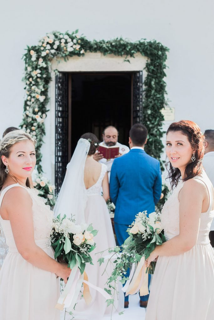 Bride and groom standing in front of the church along with bridesmaids.