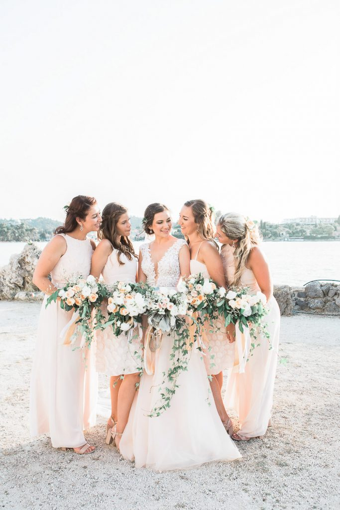 Bride and bridesmaids looking at her in front of the sea.