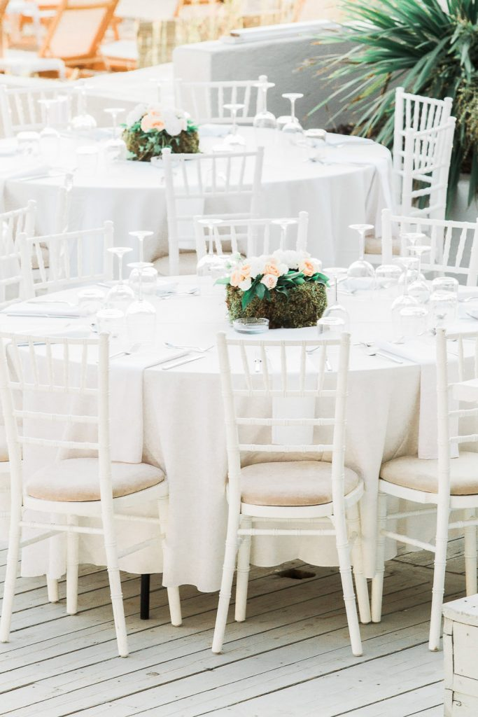 White table with white chairs and a green centrepiece in the middle.