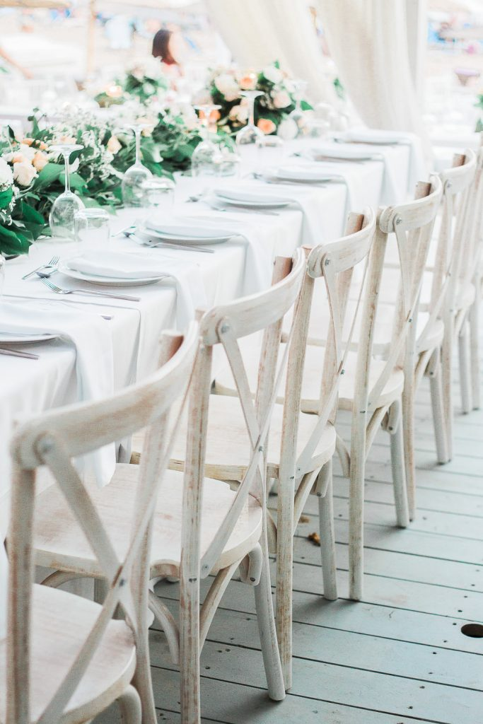 White table and white chairs decorated with roses and green leaves.