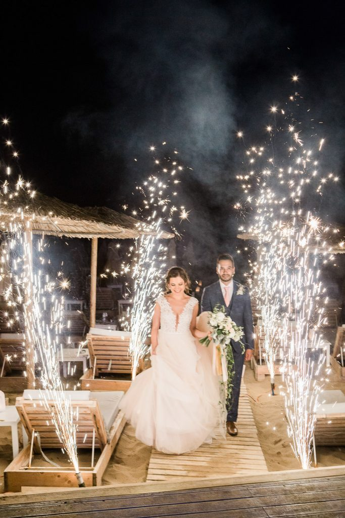 Bride and groom walking on wooden path with fireworks either side.