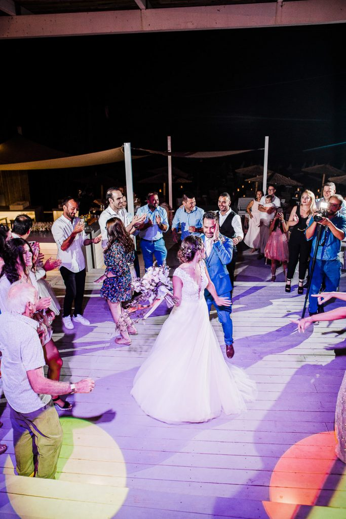 Bride and groom dancing in the middle of a wooden dance floor in between friends.