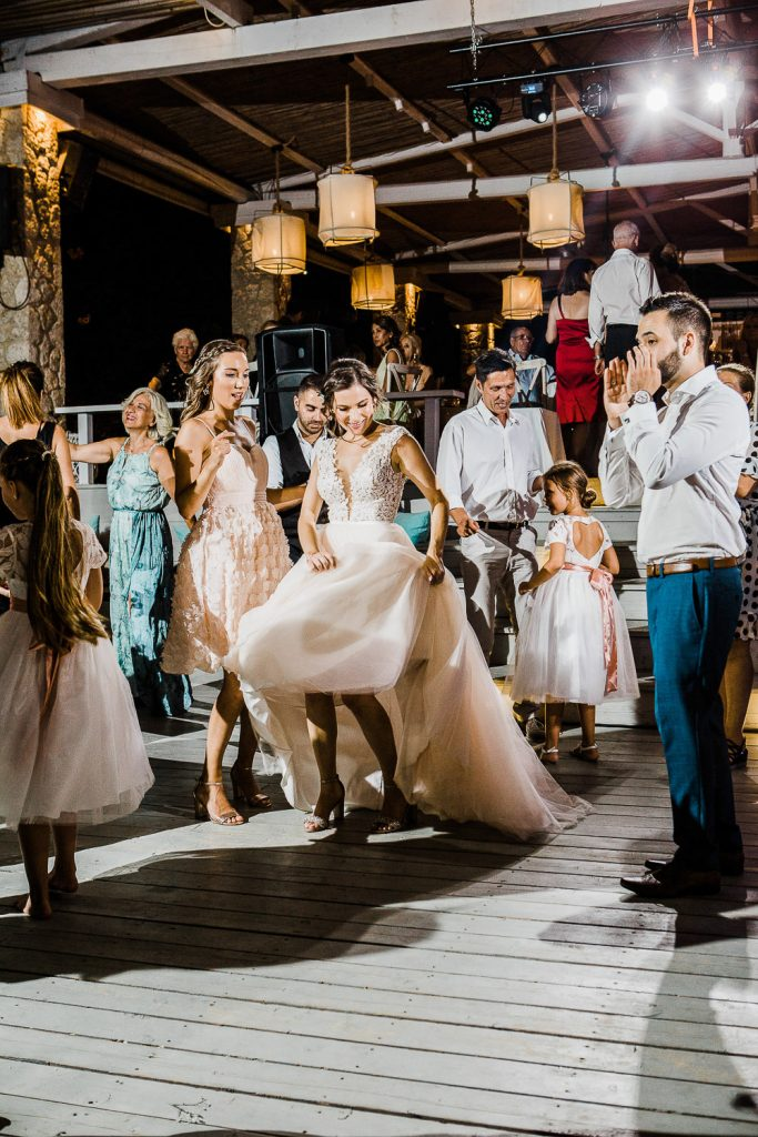 Bride dancing holding her wedding dress and groom clapping.
