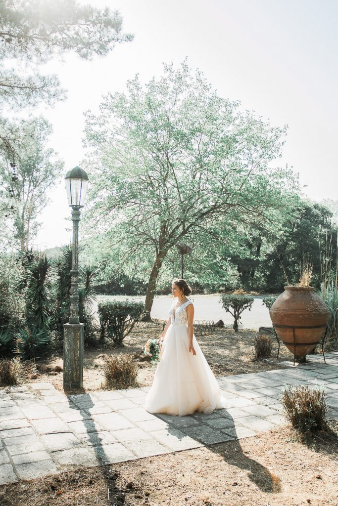 bride standing alone on a pavement holding her bouquet surrounded be trees.