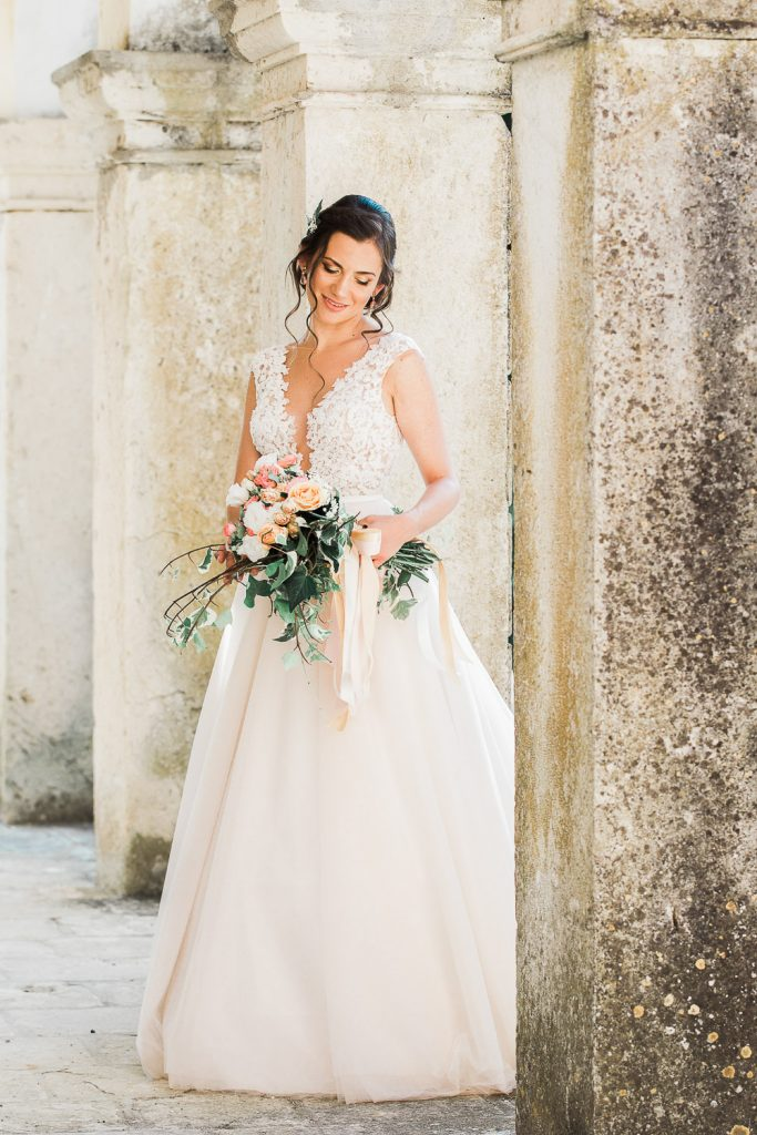 Bride standing alone looking at her bouquet in her wedding dress against a wall.