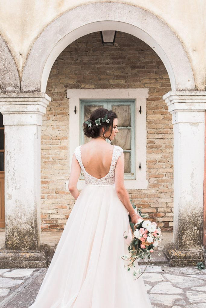 Brides back in her wedding dress holding her bouquet against an old building.