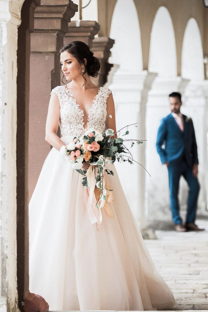 Bride in her wedding holding her bouquet against a wall and bride following her behind.