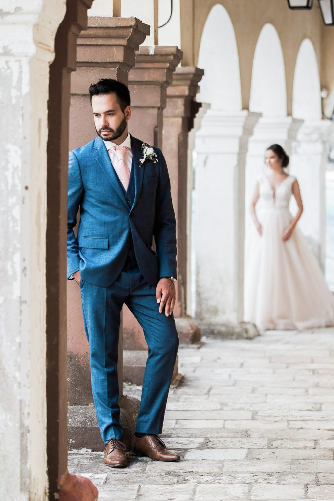 Groom in his wedding suit against a wall and bride following behind.