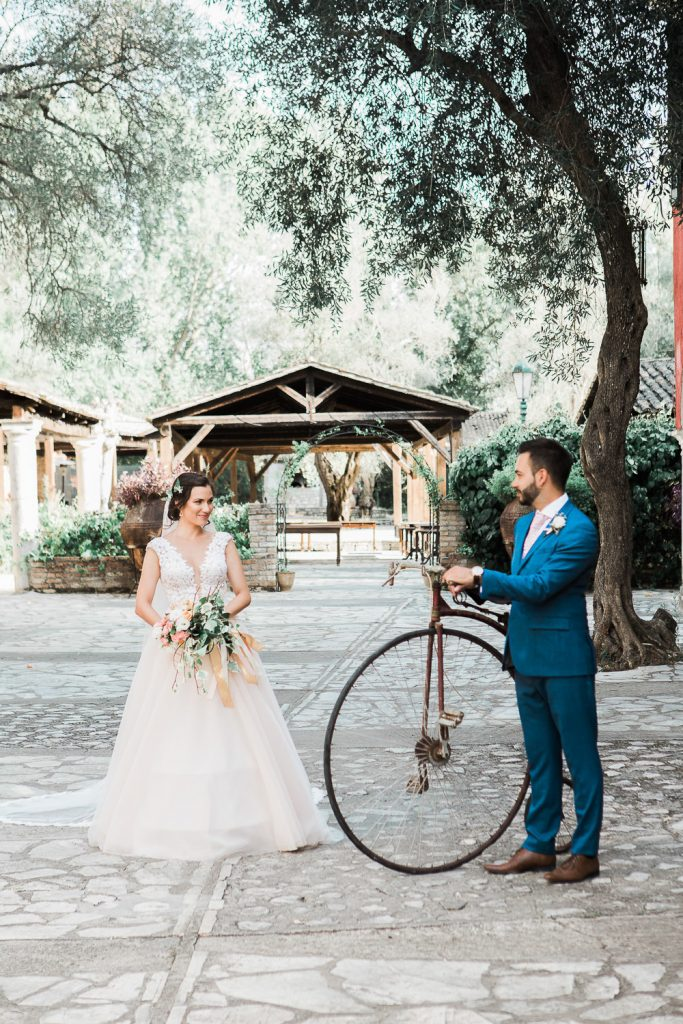 Bride holding her bouquet looking at the groom who is holding a old bicycle in Danillia Village, Corfu