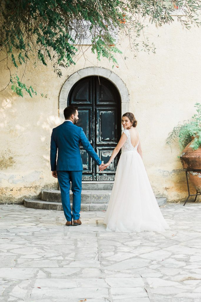 Bride and groom standing in front of a door and the bride is looking back.